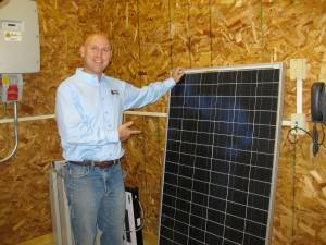 Geoff Greenfield, president of Third Sun Solar and Wind Power, stands next to a 60 kilowatt solar panel during GEO's Solar Tour. Photo by Anne Sinclair.