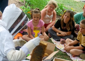 Volunteer Diana Stafford demonstrates beekeeping to local children at Hope Garden. Provided by Liz Shaw.